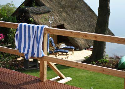 Ferienhaus am Küchensee (Ratzeburg) Geländer mit Weinglas und Handtuch 2